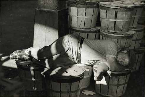 PHOTO: Man sleeping on some barrels